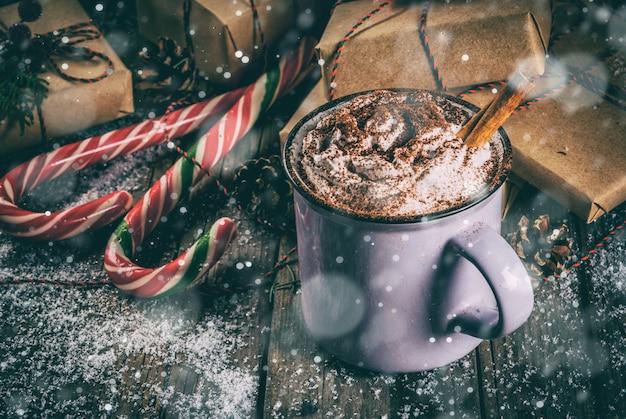 Kerstmis, warme chocolademelk of cacao met slagroom en kruiden, kerstcadeaus, snoep stokken, kerstboom tak en dennenappels, op oude rustieke houten tafel met sneeuw, copyspace afgezwakt