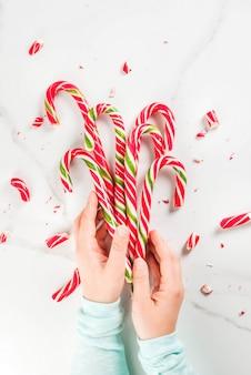 Kerstmis, winter concept. vakantie, snoep, traktaties. meisjeshanden die traditioneel suikergoedriet in de vorm van een boeket houden, geheel en in stukken gebroken. witte marmeren tafel, bovenaanzicht, copyspace