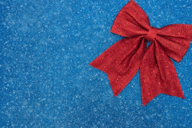 Kerstmis, winter of andere vakantie blauwe achtergrond met rode strik