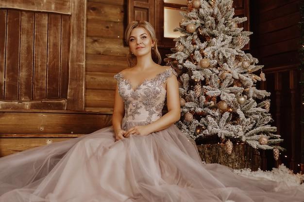 Kerstmis, wintervakantie concept. mooie vrouw in lange avondjurk poseren in luxe appartementen ingericht voor kerstmis. schoonheid, manier.