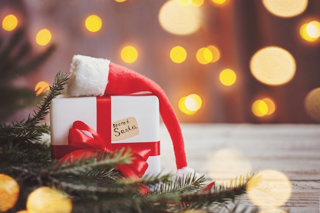 Kerstmis wit vakje of heden met rood lint voor geheime santa met kerstmuts op houten tafel.