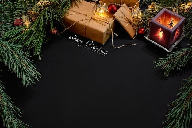 Kerstmis. xmas speelgoed en vuren tak op zwarte achtergrond bovenaanzicht. ruimte kopiëren. stilleven. plat leggen. nieuwjaar Premium Foto