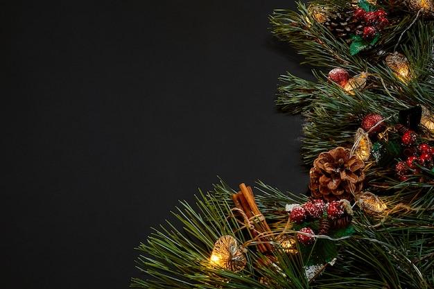 Kerstmis. xmas speelgoed en vuren tak op zwarte achtergrond bovenaanzicht. ruimte kopiëren. stilleven. plat leggen. nieuwjaar