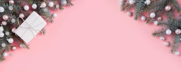 Kerstmis zilveren roze glazen bol en dennentakken op roze. kerst banner. copyspace. uitzicht van boven.