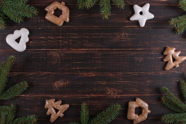 Kerstmisachtergrond, kerstbomen en peperkoek met de hand gemaakt op een houten lijst