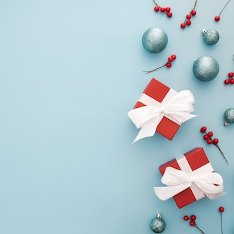 Kerstmisachtergrond met blauwe ballen, rode giften en maretak