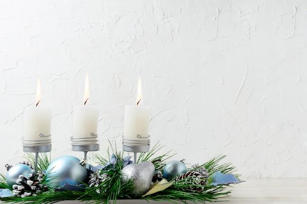 Kerstmisachtergrond met blauwe ornamenten en brandende kaarsen