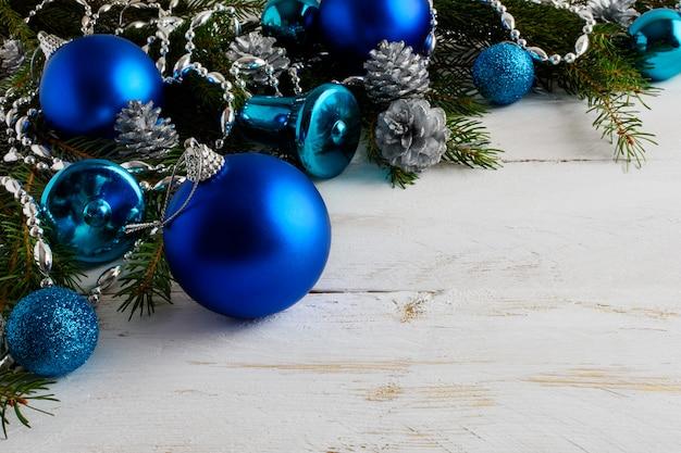 Kerstmisachtergrond met blauwe ornamenten, zilveren parels en denneappels