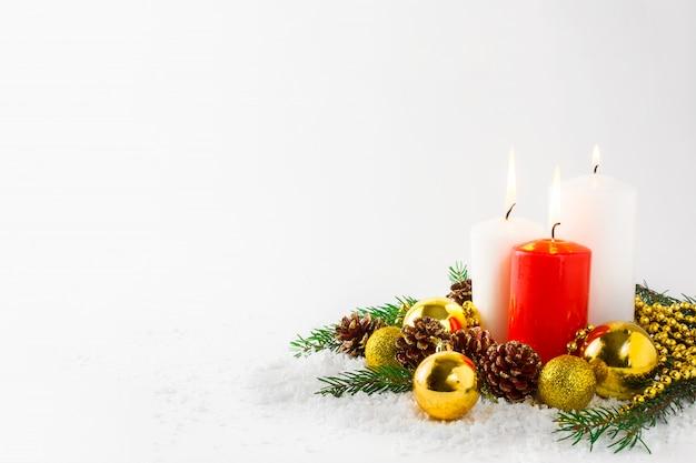 Kerstmisachtergrond met brandende kaarsen in sneeuw