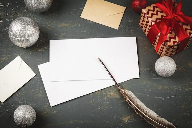 Kerstmisachtergrond met brief, envelop en veerpen die door seizoengebonden decoratie wordt omringd