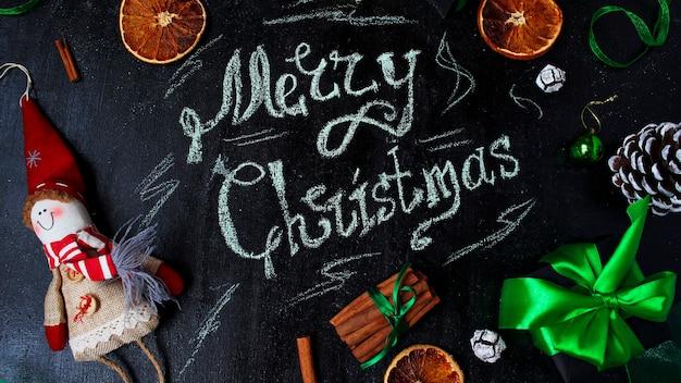 Kerstmisachtergrond met de woorden vrolijke kerstmis, droge oranje, witte pinecone, groene ballen van de kerstboom