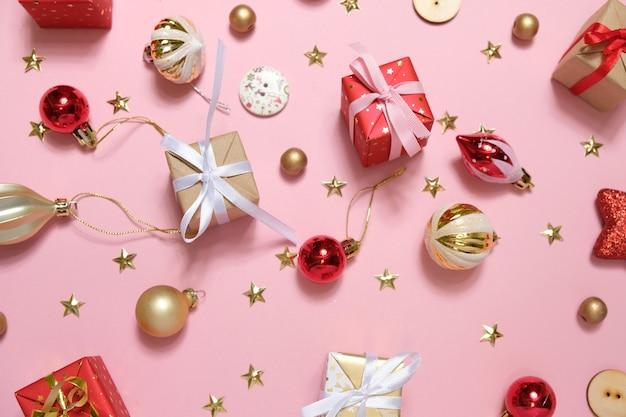 Kerstmisachtergrond met decoratie en giftdozen op roze achtergrond