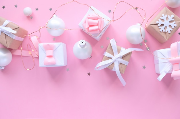 Kerstmisachtergrond met decoratie en giftdozen op roze