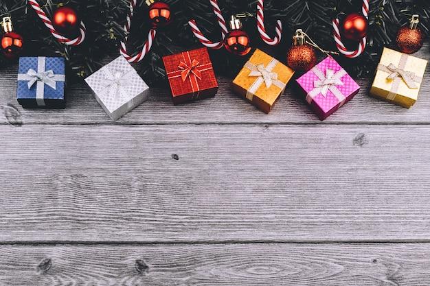 Kerstmisachtergrond met decoratie, giftvakjes, boomtakken en rode snuisterijen met abst