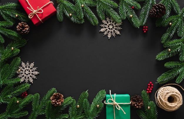 Kerstmisachtergrond met decoratie, rode en groene giften, sneeuwvlok, bessen, pijnboomtakken en kegels