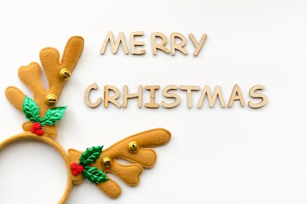 Kerstmisachtergrond met decoratieve houten teksten en kerstmishertenhoornen op wit raad
