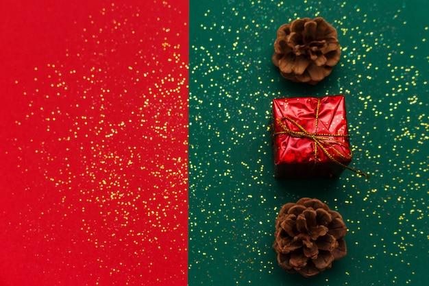 Kerstmisachtergrond met denneappels, het gouden glanzen schittert en giftdoos op traditioneel