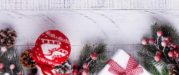 Kerstmisachtergrond met dennentakken, dennenappels en bessen op het oude witte houten bord. bovenaanzicht