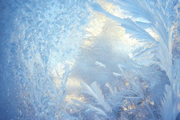 Kerstmisachtergrond met een ijzig patroon op glas