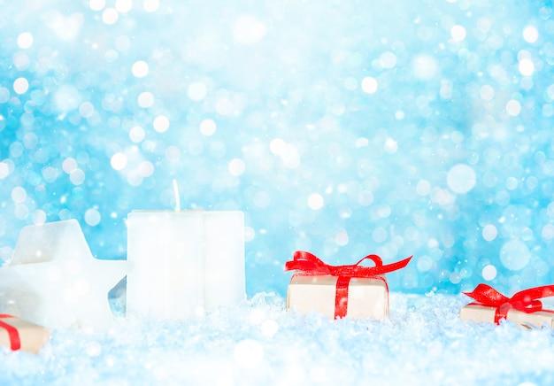 Kerstmisachtergrond met giftdozen en kaarsen op sneeuw