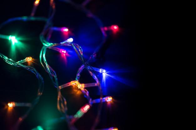 Kerstmisachtergrond met gloeiende slingers op zwarte