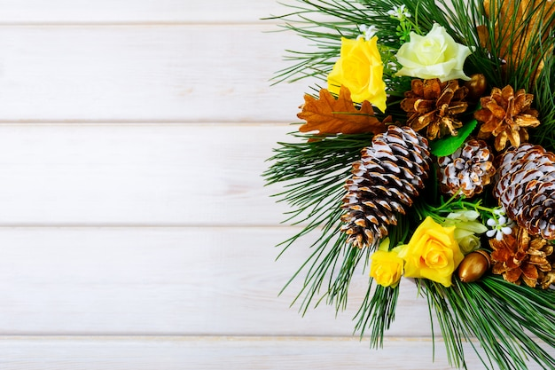 Kerstmisachtergrond met gouden denneappels en gele stoffenrozen