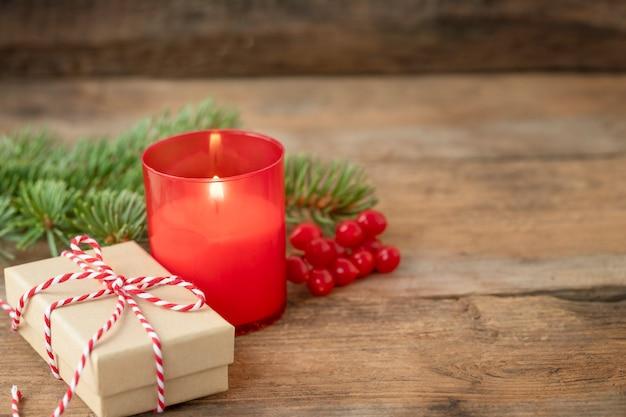 Kerstmisachtergrond met kaarslicht en giftdoos op houten backdrop
