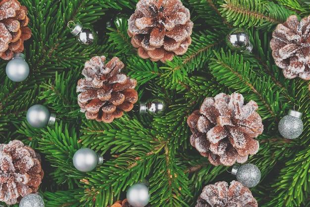 Kerstmisachtergrond met kegels en pijnboomtakken op groen