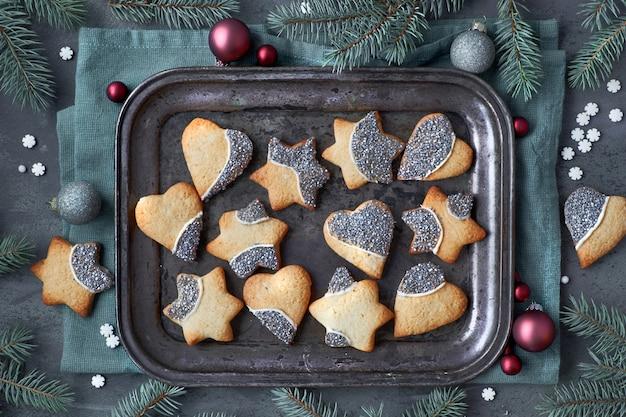 Kerstmisachtergrond met kerstmiskoekjes in vorm van harten en sterren op metaaldienblad