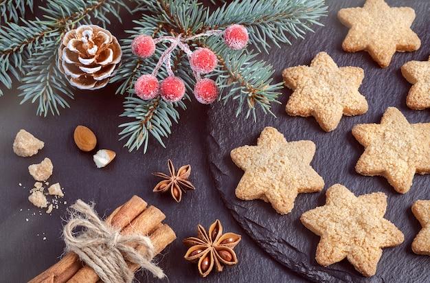 Kerstmisachtergrond met koekjes en kruiden op donkere steen