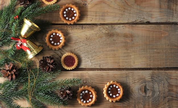 Kerstmisachtergrond met nette takken en kegels met koekjes