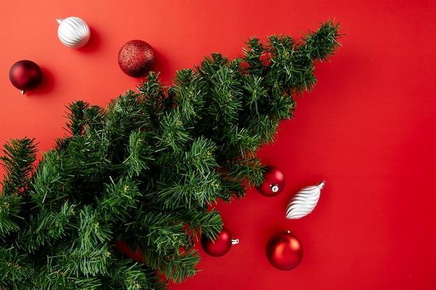 Kerstmisachtergrond met pijnboomboom en rood nieuw document met ballen