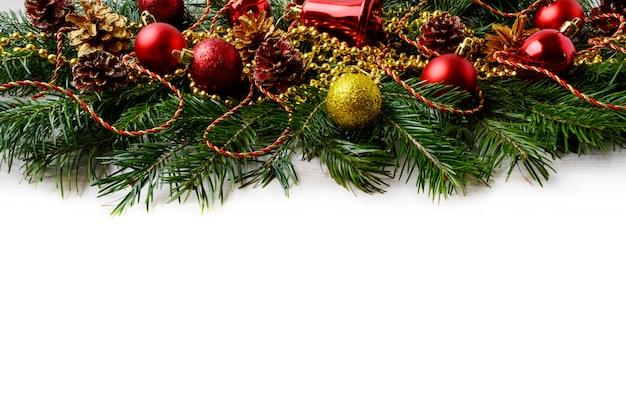 Kerstmisachtergrond met rode ornamenten en gouden verfraaide pinecone