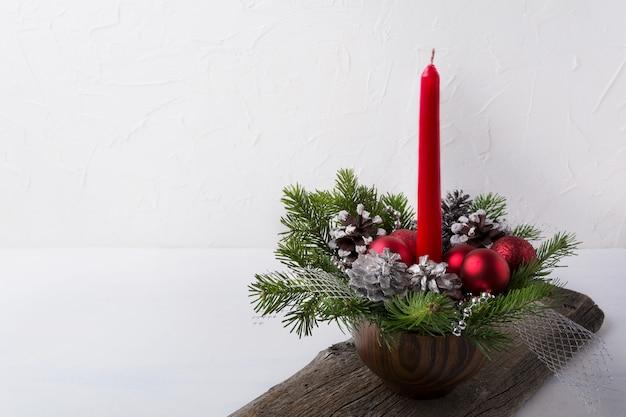 Kerstmisachtergrond met rood kaars en ornamentenbelangrijkst voorwerp