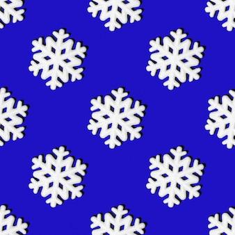 Kerstmisachtergrond met sneeuwvlokken. feestelijk naadloos patroon van witte sneeuwvlokken op een blauwe achtergrond, vierkante lay-out, bovenaanzicht. kan worden gebruikt als kerst- en nieuwjaarskaarten, textiel, inpakpapier