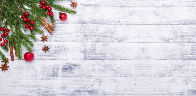 Kerstmisachtergrond met spar en rode decoratie op houten lijst. horizontale banner