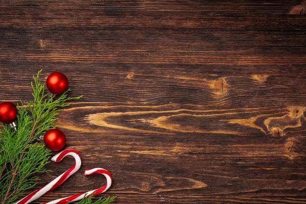 Kerstmisachtergrond met suikergoedriet op verfraaid houten bureau