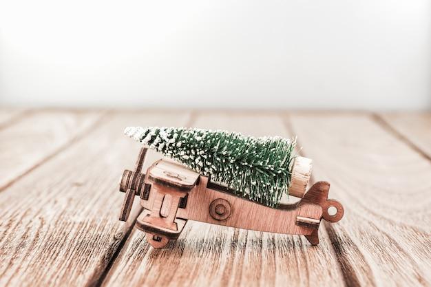 Kerstmisachtergrond met uitstekend houten vliegtuigstuk speelgoed met miniatuurpijnboom
