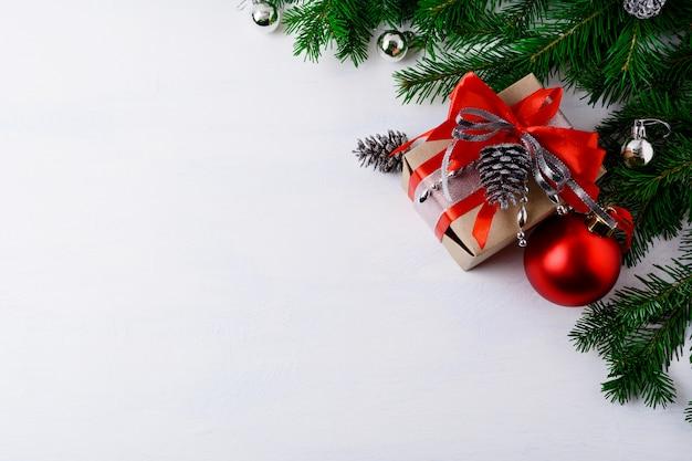 Kerstmisachtergrond met verfraaide giftdoos en zilveren denneappels