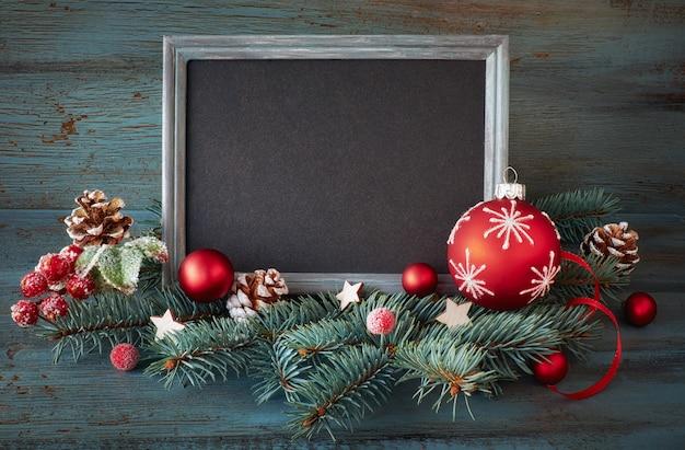 Kerstmisachtergrond met verfraaide sparrentakjes rond schoolbord op hout