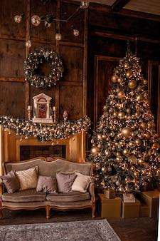 Kerstmisachtergrond met verlichte spar met gouden decpration en open haard in woonkamer. gezellig vakantiehuis