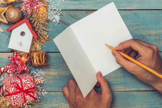 Kerstmisachtergrond met versieringen met hand die op wenskaarten schrijven. bovenaanzicht met kopieerruimte