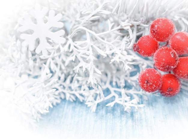 Kerstmisachtergrond met witte nette takken en sneeuwvlokken op een blauwe houten achtergrond