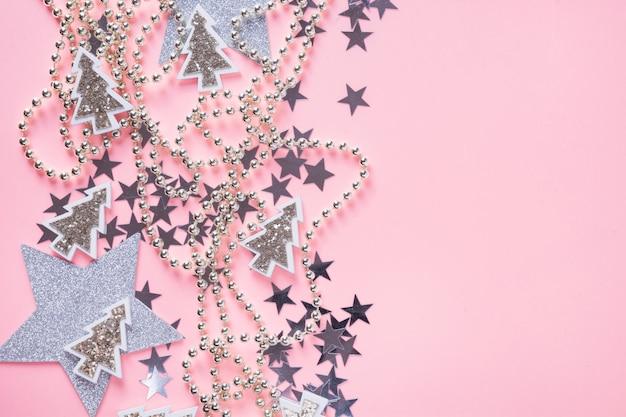 Kerstmisachtergrond met zilveren ballen, sterren op roze