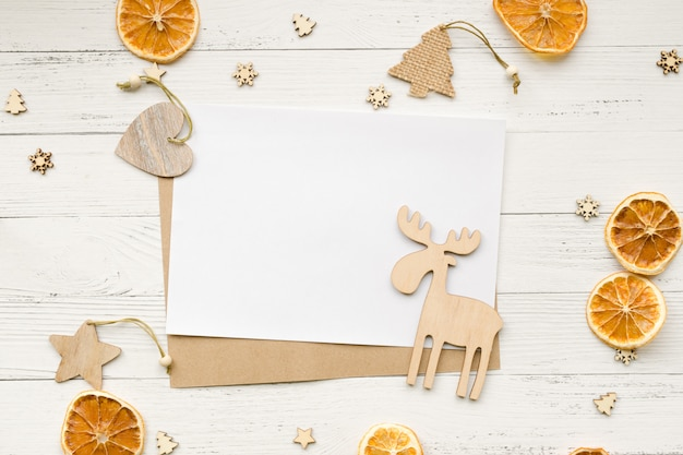 Kerstmisachtergrond van droge sinaasappelen, kerstmisdecoratie en lege witte kaart voor groeten op een houten lijst. sterren, harten en elanden. bovenaanzicht copyspace.