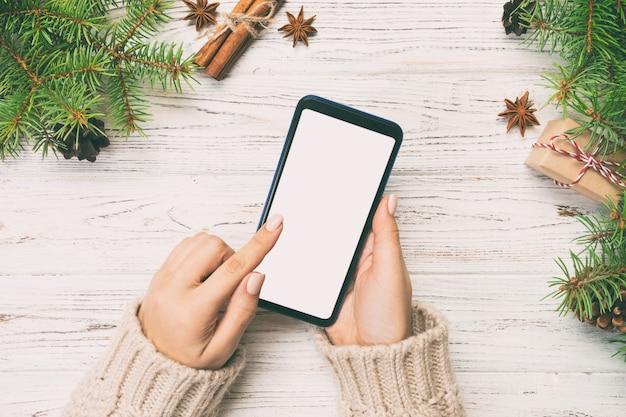 Kerstmisachtergrond: vrouwelijke smartphone van het handenoverseinen op rustieke houten lijst