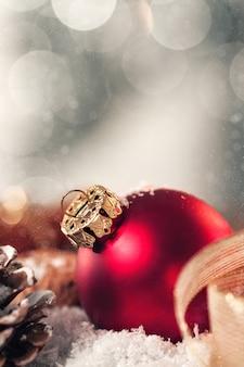 Kerstmisbal met decoratie met kaarsen, sparappel, noten, sneeuw en lint, gestemde close-up