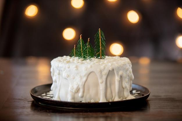 Kerstmiscake met room op lijst met feelichten