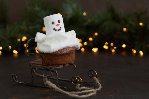 Kerstmischocolade cupcakes met sneeuwmandecor. op een donkere achtergrond.
