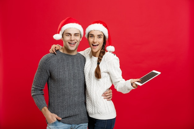 Kerstmisconcept - gelukkig jong paar dat in kerstmissweaters digitale tablet houdt.
